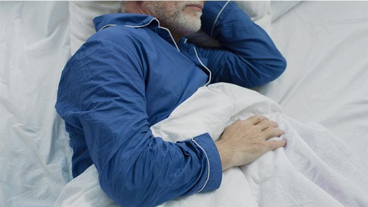 man in bed wearing blue pajamas