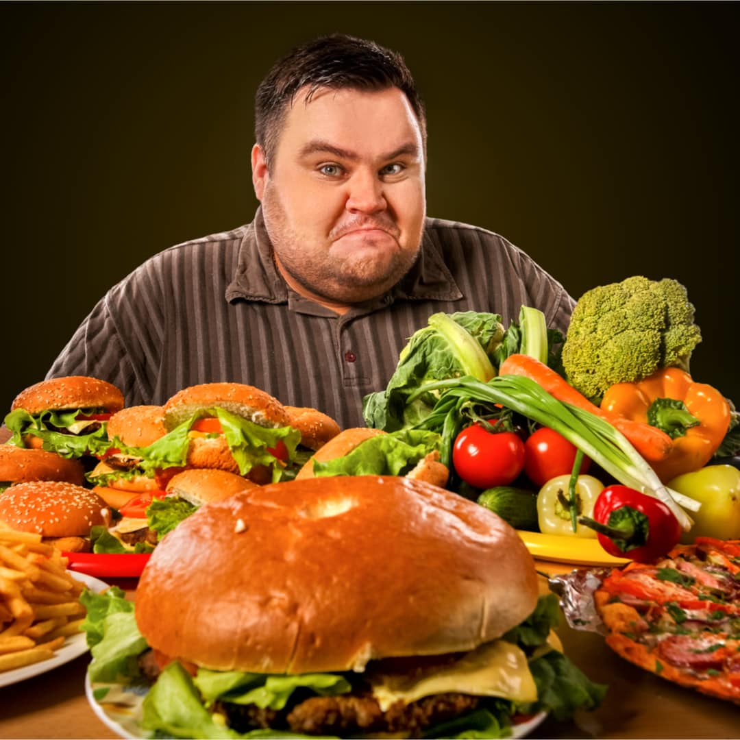 man with determined look sitting in front of piles of hamburgers french fries, pizza, and fresh vegetables