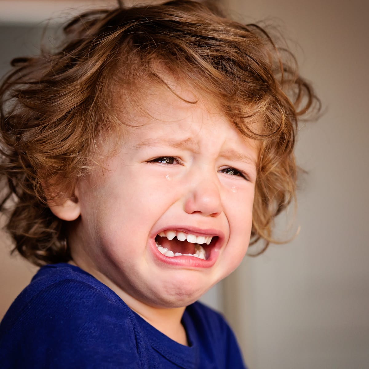 toddler boy in blue shirt with curly hair crying
